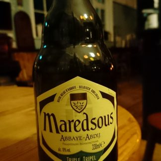 Stubby brown bottle on the edge of a wooden table