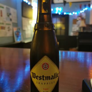 Brown bottle with a yellow diamond label reading Westmalle sits on a polished wooden surface